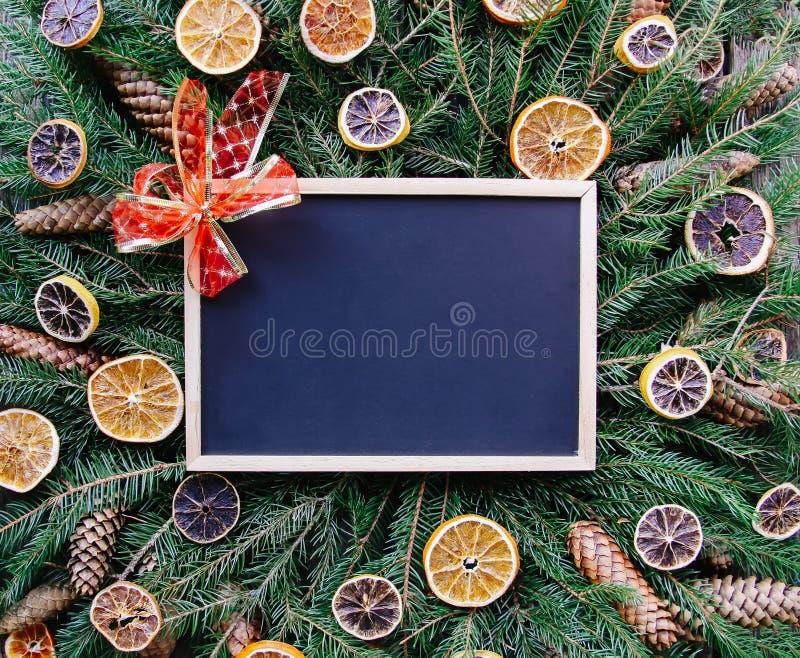 Χριστούγεννα, νέα σύνθεση χειμερινών διακοπών έτους Ο κενός πλαισιωμένος πίνακας στους πράσινους fir-tree κλάδους που διακοσμούντ στοκ φωτογραφίες με δικαίωμα ελεύθερης χρήσης