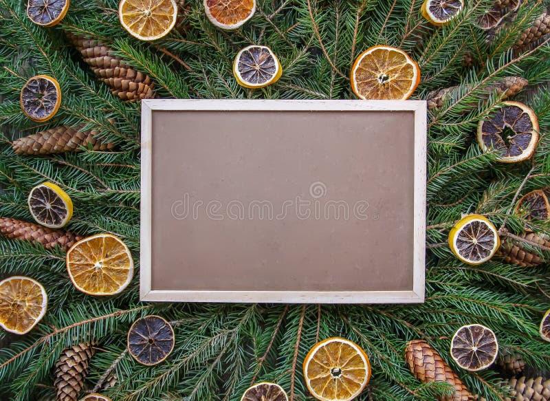 Χριστούγεννα, νέα σύνθεση χειμερινών διακοπών έτους Ο κενός πλαισιωμένος πίνακας στους πράσινους fir-tree κλάδους που διακοσμούντ στοκ φωτογραφίες