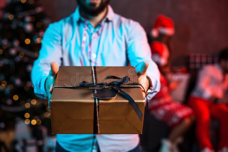 Χριστούγεννα, Χριστούγεννα, νέο έτος, χειμώνας, έννοια ευτυχίας - χαμογελώντας άτομο στο καπέλο αρωγών santa με το κιβώτιο δώρων στοκ εικόνες με δικαίωμα ελεύθερης χρήσης
