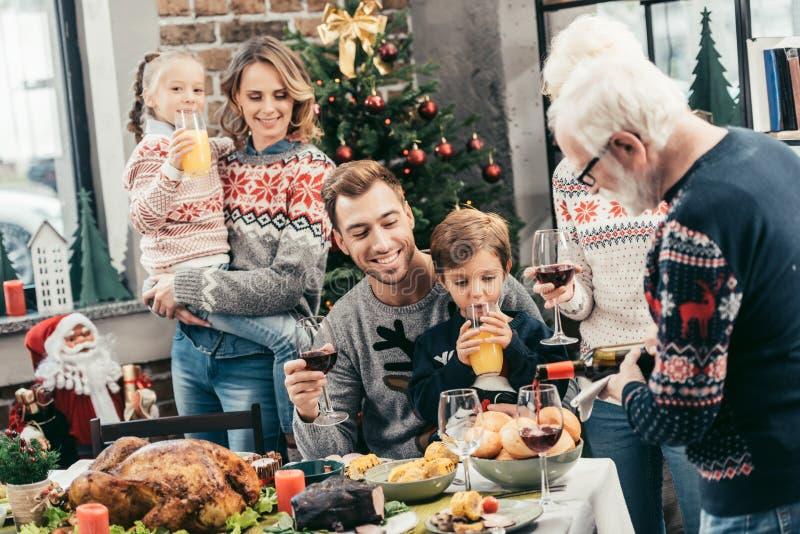 Χριστούγεννα οικογενειακού εορτασμού μαζί ενώ χύνοντας κρασί grandpa στοκ φωτογραφία με δικαίωμα ελεύθερης χρήσης