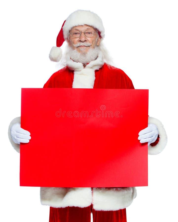 Χριστούγεννα Ο καλός Άγιος Βασίλης στα άσπρα γάντια κρατά ένα κενό χαρτόνι του κόκκινου χρώματος Θέση για τη διαφήμιση, για το κε στοκ φωτογραφίες