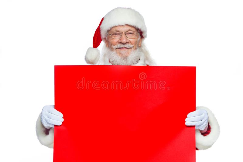 Χριστούγεννα Ο καλός Άγιος Βασίλης στα άσπρα γάντια κρατά ένα κενό χαρτόνι του κόκκινου χρώματος Θέση για τη διαφήμιση, για το κε στοκ φωτογραφίες με δικαίωμα ελεύθερης χρήσης