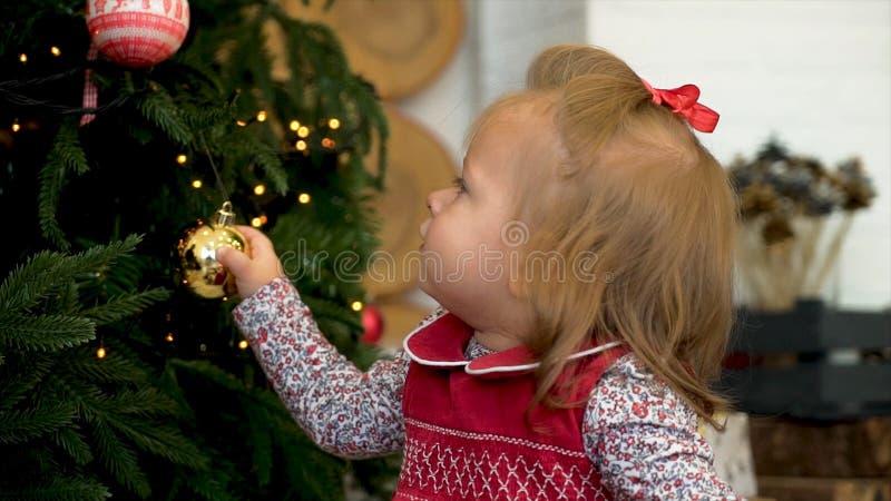 Χριστούγεννα που διακο& Παιχνίδι μικρών κοριτσιών με το παιχνίδι στο χριστουγεννιάτικο δέντρο στοκ εικόνες