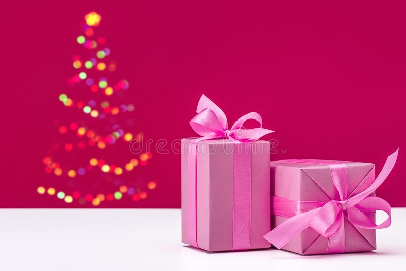 Χριστούγεννα πυράκτωσης, νέο δέντρο έτους στο ρόδινο υπόβαθρο Δώρα στο ρόδινο έγγραφο με τις κορδέλλες στοκ εικόνες