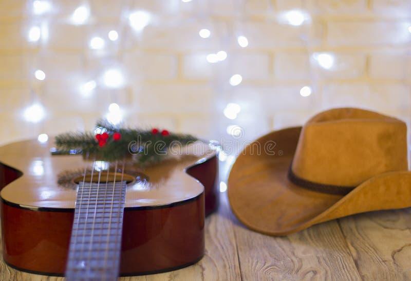 Χριστούγεννα country μουσικής με το καπέλο κιθάρων και κάουμποϋ στοκ φωτογραφίες