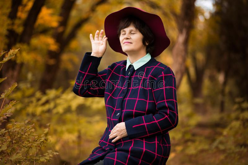 60χρονη γυναίκα στα κόκκινα όνειρα καπέλων στο χρυσό πάρκο φθινοπώρου στοκ φωτογραφία με δικαίωμα ελεύθερης χρήσης