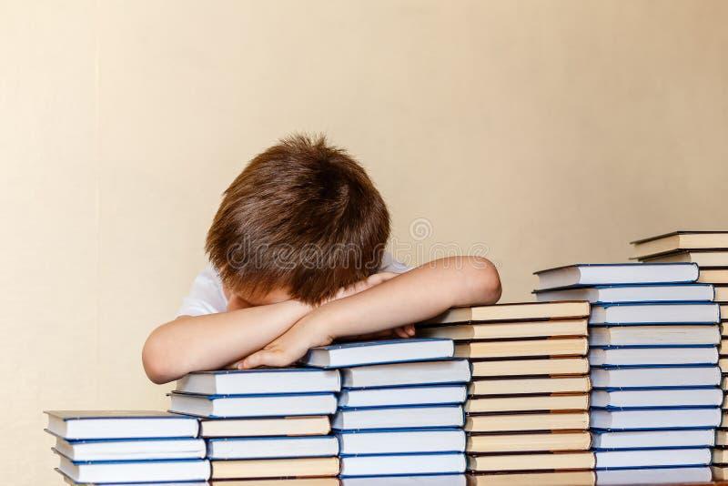 6χρονη συνεδρίαση αγοριών στον πίνακα, τα χέρια και το κεφάλι του στο βιβλίο στοκ εικόνα