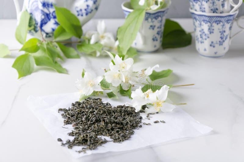 Χρονική έννοια τσαγιού Τα φλυτζάνια και teapot, το πράσινο τσάι και φρέσκο jasmine ανθίζουν στον άσπρο πίνακα στοκ εικόνα με δικαίωμα ελεύθερης χρήσης