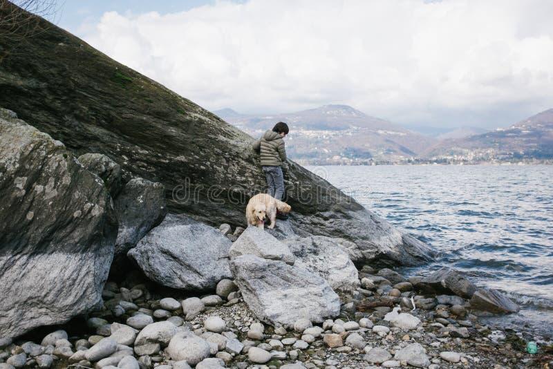 12χρονο αγόρι με το παιχνίδι σκυλιών του κοντά σε έναν λίθο στοκ φωτογραφίες με δικαίωμα ελεύθερης χρήσης