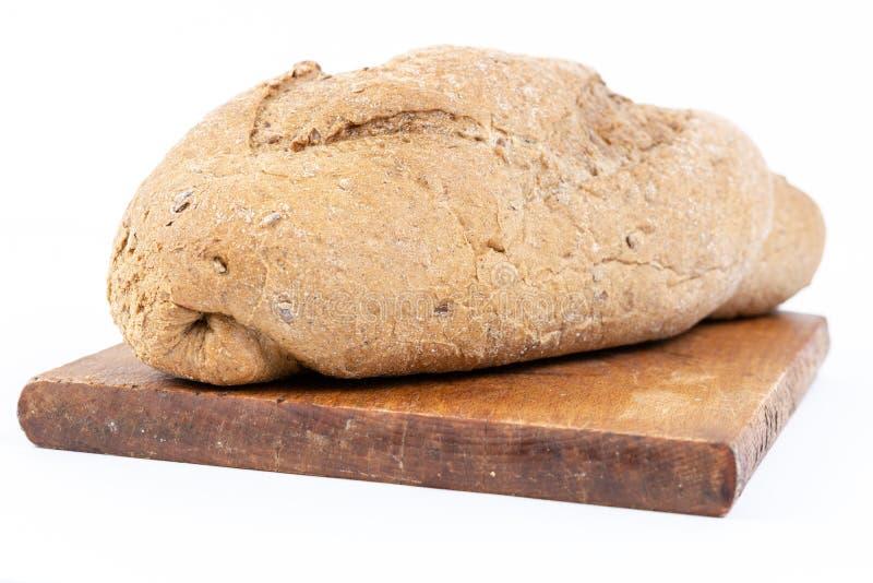 Χρονο ψωμί με τα δημητριακά στον ξύλινο τέμνοντα πίνακα στοκ φωτογραφία