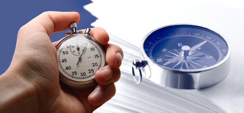 Χρονόμετρο με διακόπτη εκμετάλλευσης χεριών, κάρτες εγγράφου και πυξίδα στοκ φωτογραφίες