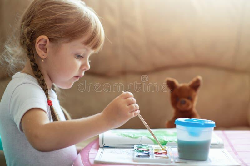 Χρονών καυκάσια εικόνα χρωματισμού κοριτσιών ελάχιστα τέσσερα από τη συνεδρίαση χρωμάτων στον πίνακα, ανάπτυξη παιδιών στοκ φωτογραφία
