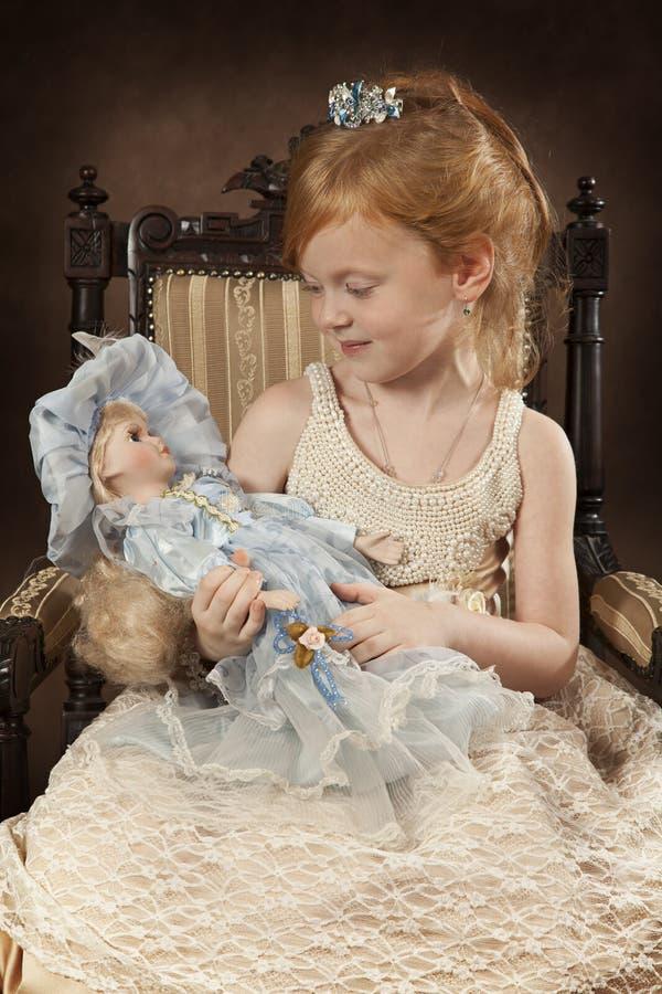 Χρονών κορίτσι τέσσερα με μια κούκλα στοκ εικόνες