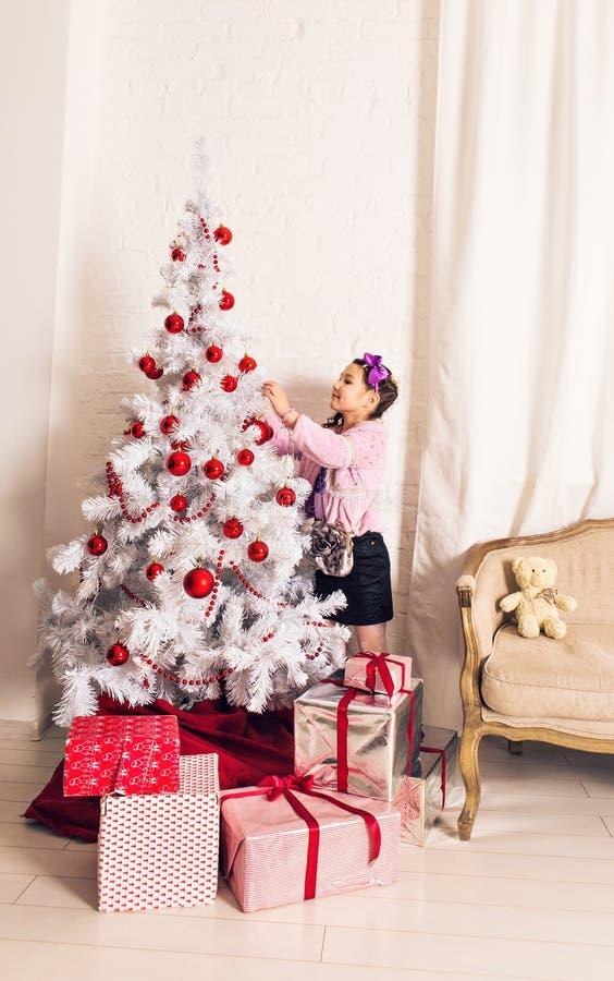 8 χρονών μικρό κορίτσι που διακοσμεί το χριστουγεννιάτικο δέντρο στο σπίτι στοκ φωτογραφίες