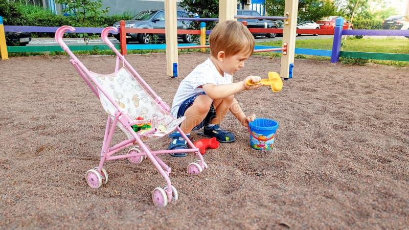 3 χρονών μικρό παιδί με το καροτσάκι παιχνιδιών για τις κούκλες που παίζει στην παιδική χαρά στο πάρκο στοκ φωτογραφία με δικαίωμα ελεύθερης χρήσης