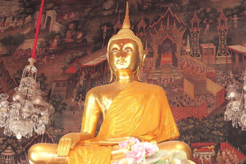 Χρυσά αγάλματα του Βούδα και ντυμένος στην κίτρινη τήβεννο στοκ εικόνες