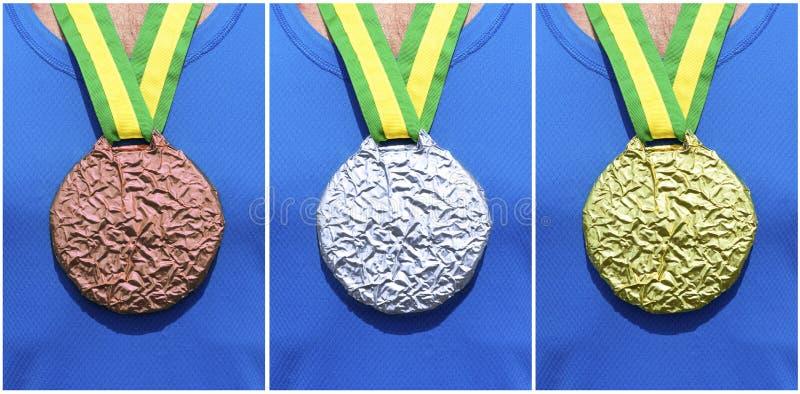 Χρυσά ασημένια χάλκινα μετάλλια στον αθλητή στοκ φωτογραφίες με δικαίωμα ελεύθερης χρήσης