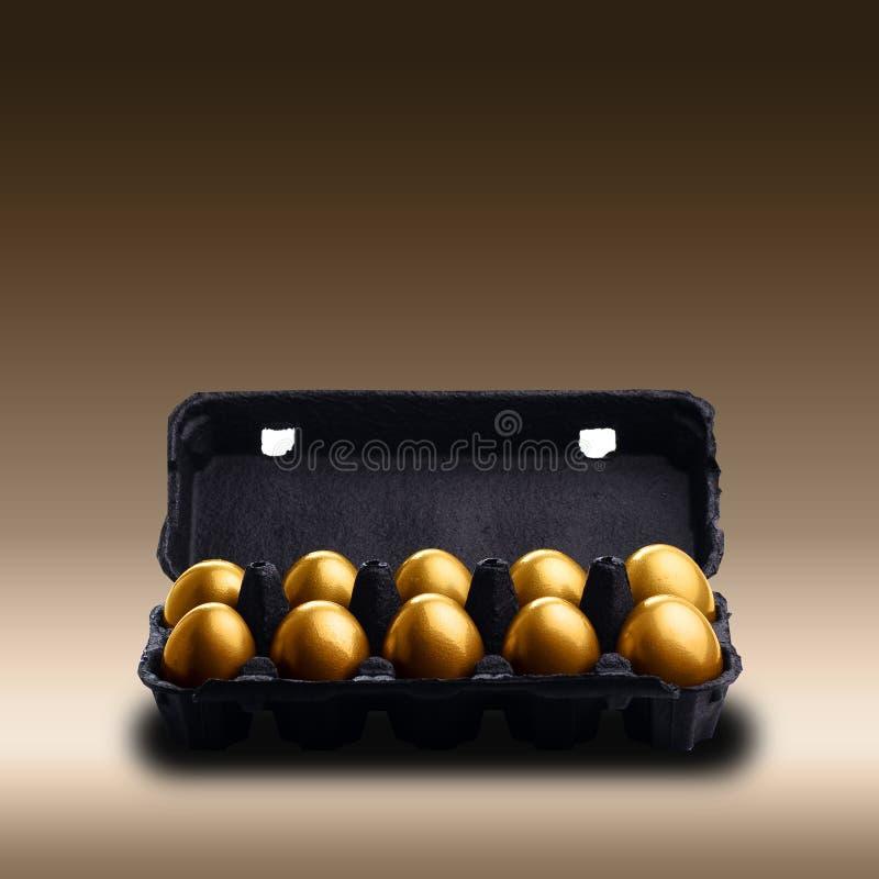 Χρυσά αυγά σε ένα μαύρο χαρτοκιβώτιο στοκ εικόνες