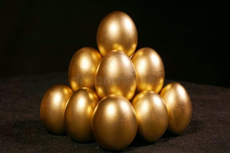 Χρυσά αυγά στο μαύρο υπόβαθρο στοκ εικόνες