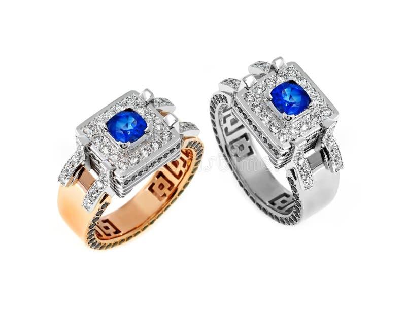 Χρυσά δαχτυλίδια με τα διαμάντια και το σάπφειρο στοκ εικόνες