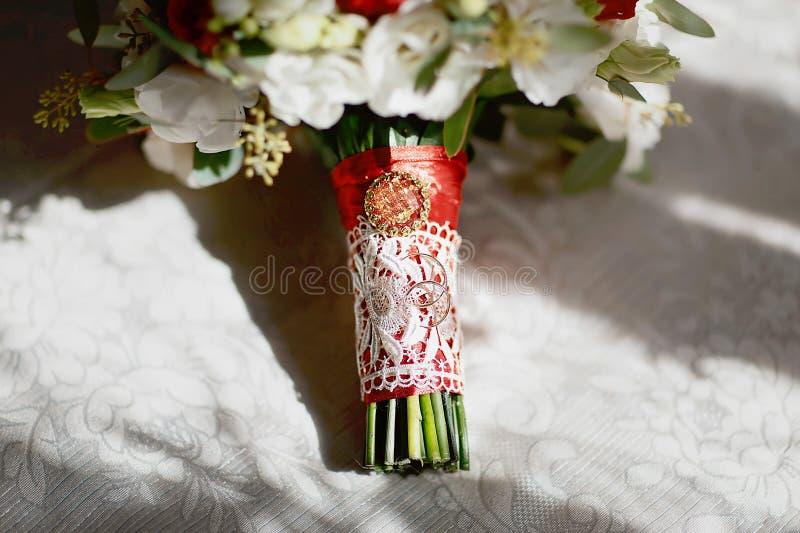 Χρυσά γαμήλια δαχτυλίδια σε μια ανθοδέσμη των λουλουδιών με την άσπρη δαντέλλα και μια κόκκινες κορδέλλα και μια πόρπη στοκ εικόνα με δικαίωμα ελεύθερης χρήσης