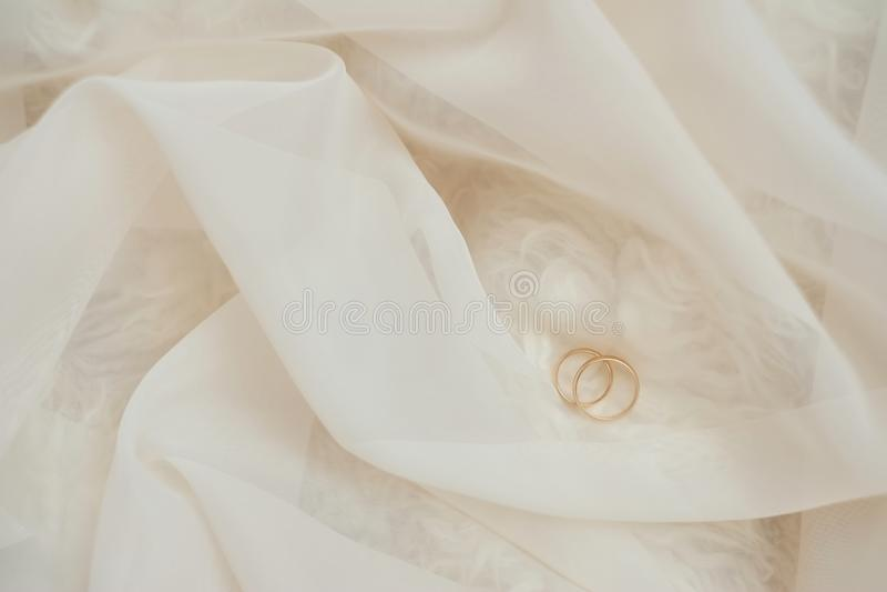 Χρυσά γαμήλια δαχτυλίδια στη δαντέλλα κρητιδογραφιών εστίαση ρηχή στοκ φωτογραφία με δικαίωμα ελεύθερης χρήσης