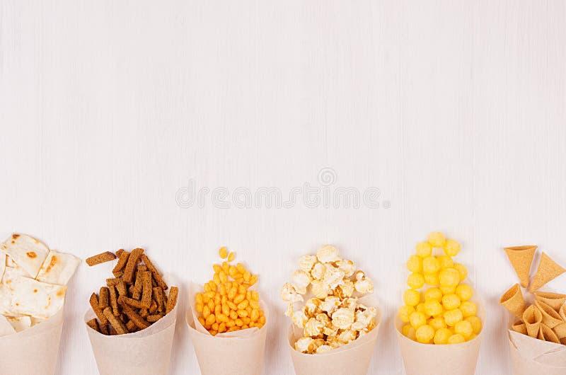 Χρυσά διαφορετικά πρόχειρα φαγητά στον κώνο εγγράφου τεχνών στο μαλακό άσπρο ξύλινο υπόβαθρο, τοπ άποψη, σύνορα στοκ εικόνα με δικαίωμα ελεύθερης χρήσης