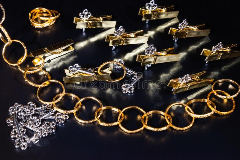 Χρυσά ειδώλια, χρυσά δαχτυλίδια, ασημένια κλειδιά, clothespins στοκ φωτογραφία
