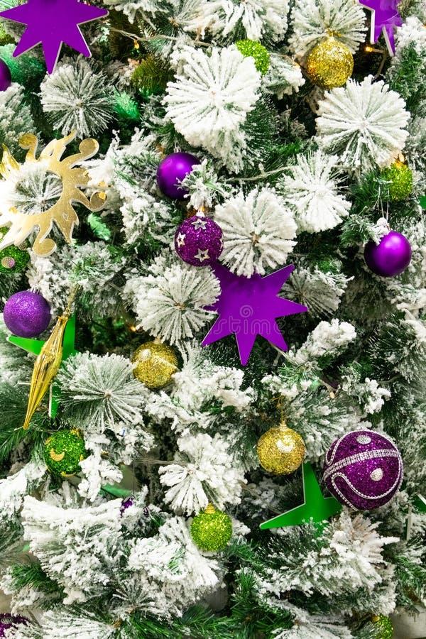 Χρυσά και ιώδη σφαίρες και αστέρια στο χριστουγεννιάτικο δέντρο Φωτεινό αφηρημένο υπόβαθρο για το σχέδιο του νέου έτους και στοκ εικόνα με δικαίωμα ελεύθερης χρήσης
