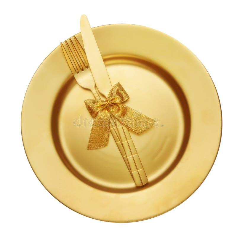 Χρυσά μαχαίρι και δίκρανο με το πιάτο στοκ φωτογραφία με δικαίωμα ελεύθερης χρήσης