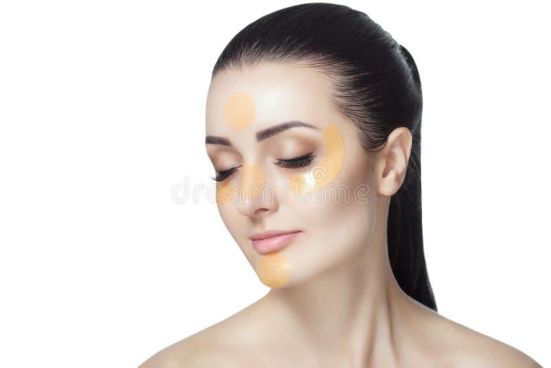 Χρυσά μπαλώματα κολλαγόνων στο δέρμα του βλέφαρου, του μετώπου και του πηγουνιού στο πρόσωπο στοκ εικόνα