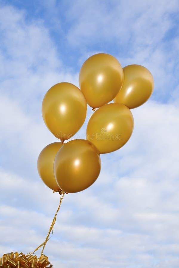 Χρυσά πετώντας μπαλόνια στην ανασκόπηση ουρανού στοκ εικόνα με δικαίωμα ελεύθερης χρήσης