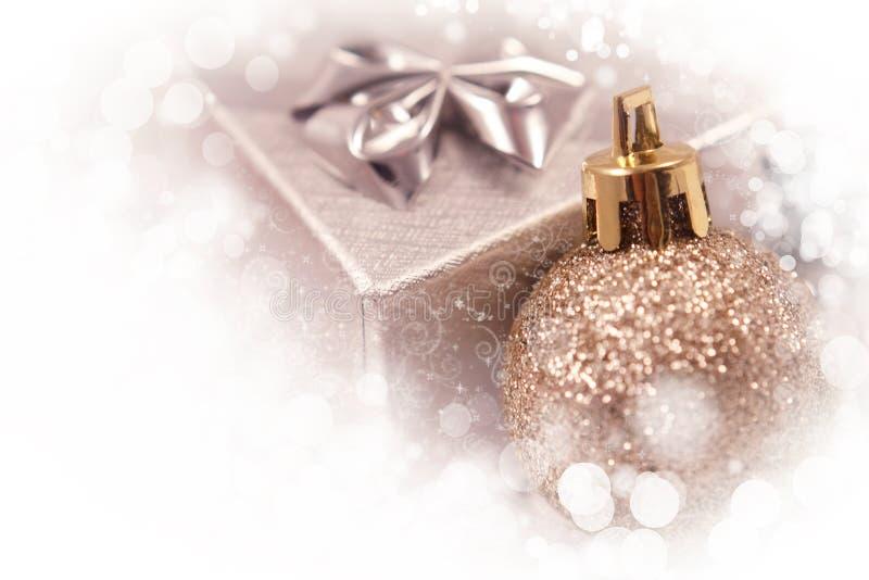 Χρυσά σφαίρα Χριστουγέννων και κιβώτιο δώρων στο άσπρο υπόβαθρο στοκ εικόνα