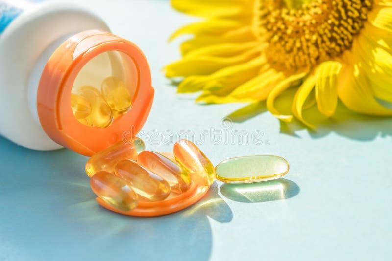 Χρυσά Sunscreen χάπια με το μπουκάλι και τον ηλίανθο στο μπλε backgro στοκ φωτογραφία