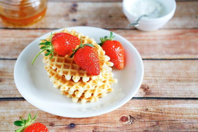 Χρυσές βάφλες με τις φράουλες και το μέλι στοκ φωτογραφία