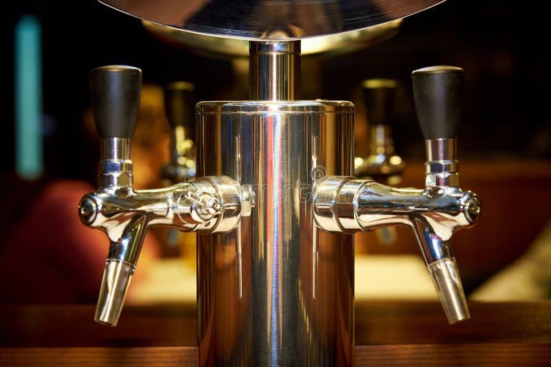Χρυσές βρύσες για την εμφιάλωση της μπύρας σε ένα μουτζουρωμένο υπόβαθρο στοκ εικόνα
