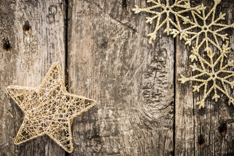 Χρυσές διακοσμήσεις χριστουγεννιάτικων δέντρων στο ξύλο grunge στοκ εικόνα