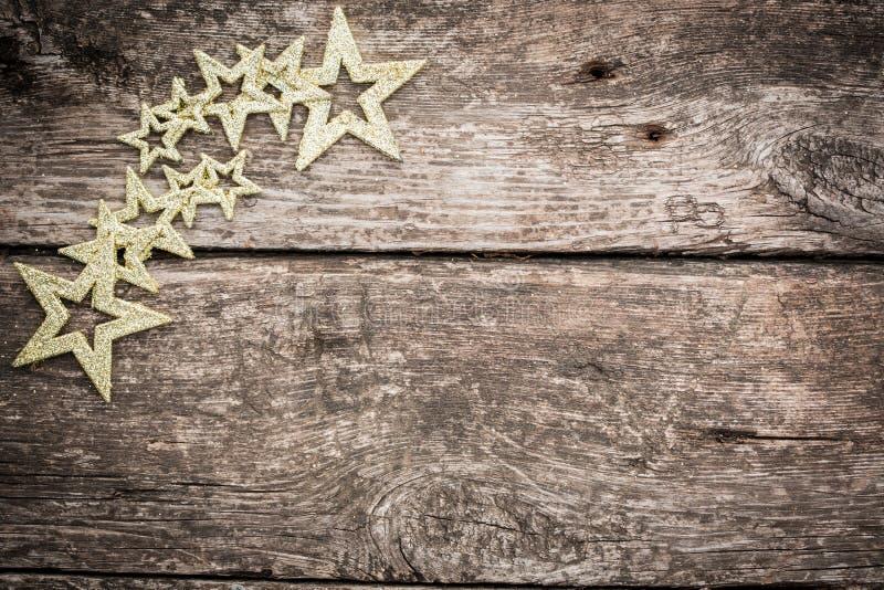 Χρυσές διακοσμήσεις χριστουγεννιάτικων δέντρων στο ξύλο grunge στοκ φωτογραφίες