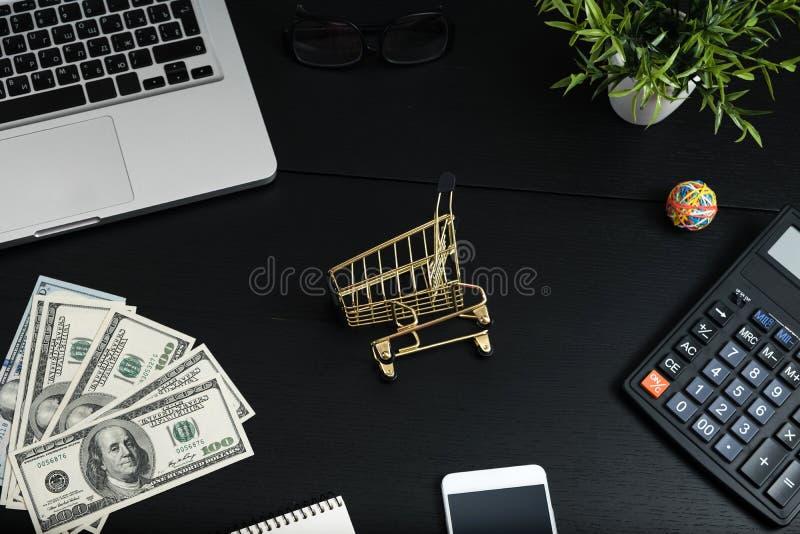 Χρυσές κάρρο, μετρητά και συσκευές σε έναν μαύρο πίνακα στοκ φωτογραφία