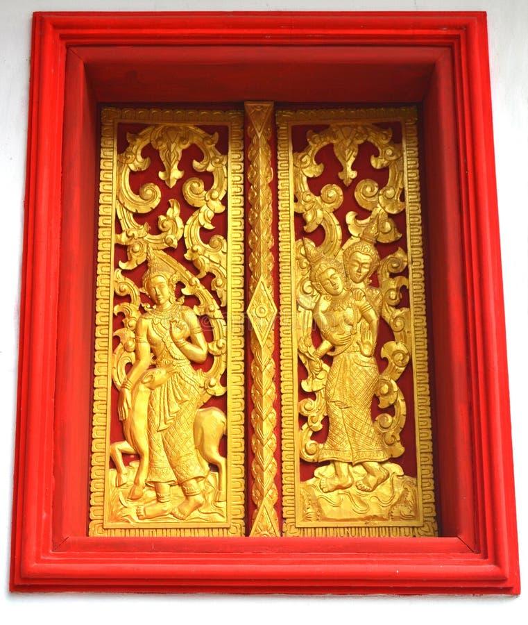 Χρυσές τοιχογραφίες αγαλμάτων και χάραξη στους βουδιστικούς ναούς Luang Prabang Λάος στοκ εικόνα