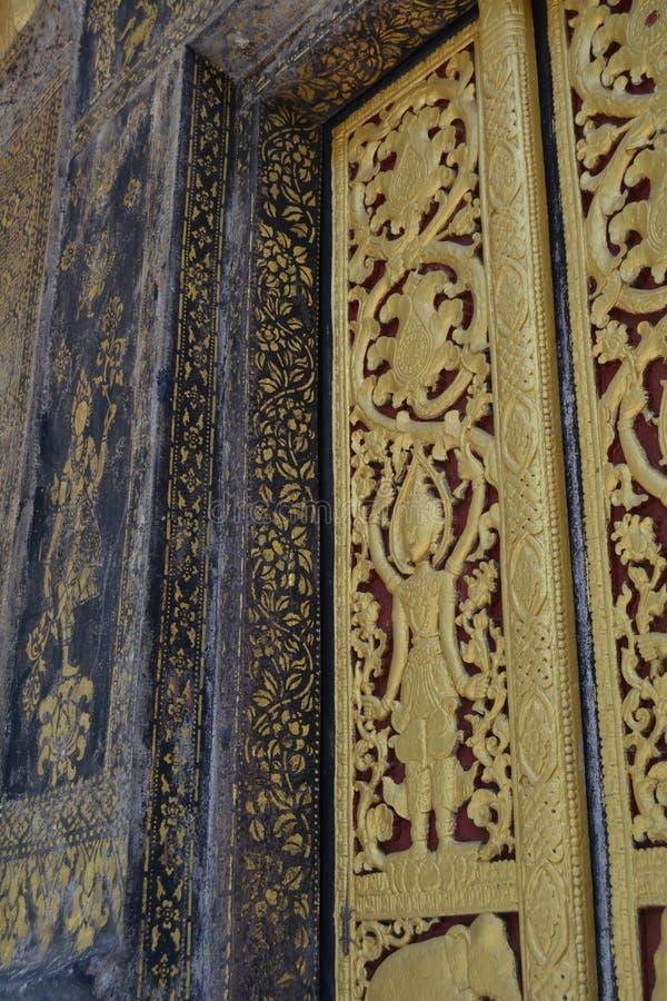 Χρυσές τοιχογραφίες αγαλμάτων και χάραξη στους βουδιστικούς ναούς Luang Prabang Λάος στοκ εικόνα με δικαίωμα ελεύθερης χρήσης