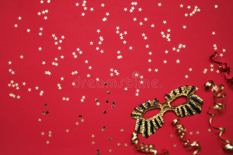 Χρυσή ακτινοβολώντας μάσκα, αστέρια κομφετί και serpentine με τα χρυσά αστέρια στο φωτεινό κόκκινο υπόβαθρο Τοπ άποψη, διάστημα α στοκ φωτογραφίες με δικαίωμα ελεύθερης χρήσης