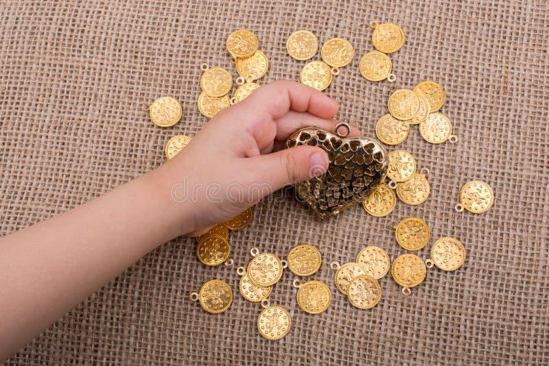 Χρυσή καρδιά υπό εξέταση με τα πλαστά νομίσματα γύρω στοκ εικόνες