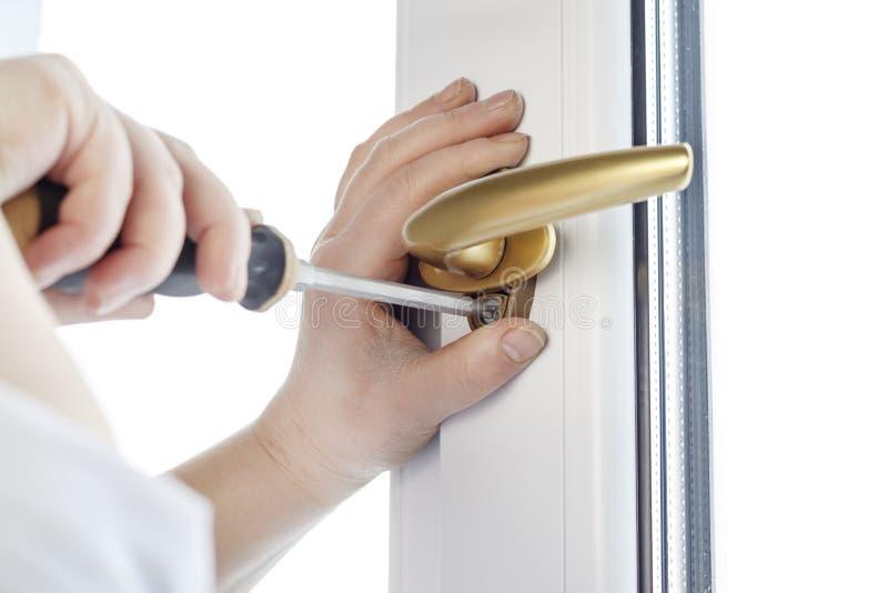 Χρυσή μάνδρα Στερεώστε τη βίδα λαβών παραθύρων στο παράθυρο PVC στοκ φωτογραφία