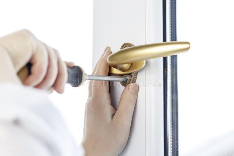 Χρυσή μάνδρα Στερεώστε τη βίδα λαβών παραθύρων στο παράθυρο PVC στοκ φωτογραφίες με δικαίωμα ελεύθερης χρήσης