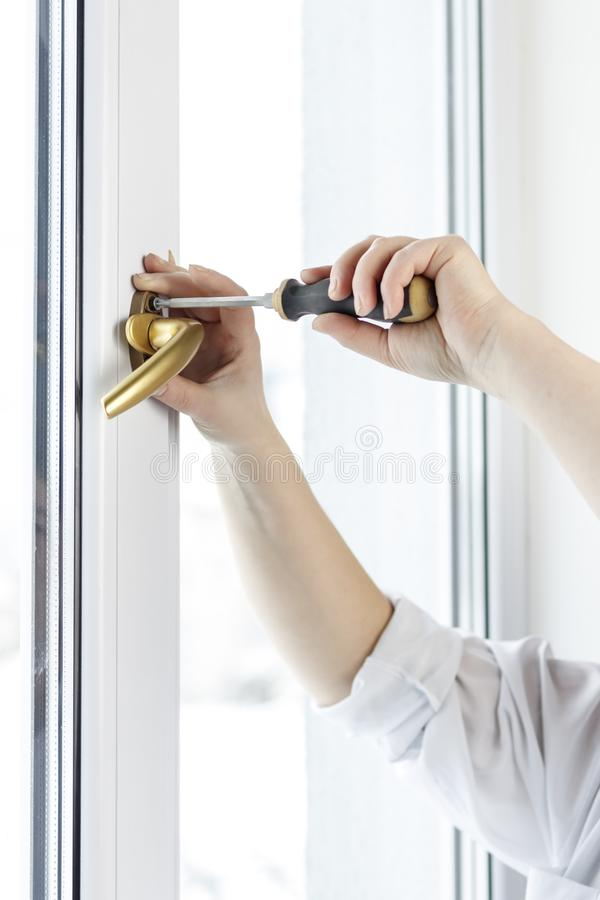 Χρυσή μάνδρα Στερεώστε τη βίδα λαβών παραθύρων στο παράθυρο PVC στοκ εικόνα με δικαίωμα ελεύθερης χρήσης