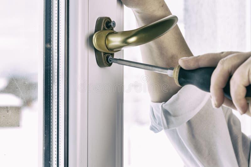 Χρυσή μάνδρα Στερεώστε τη βίδα λαβών παραθύρων στο παράθυρο PVC στοκ εικόνες