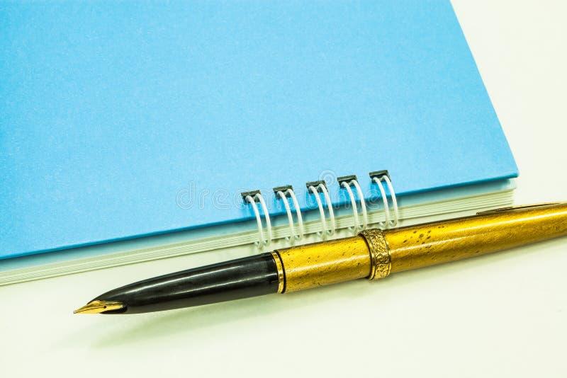 Χρυσή μάνδρα πηγών και μπλε σημειωματάριο στοκ εικόνες με δικαίωμα ελεύθερης χρήσης