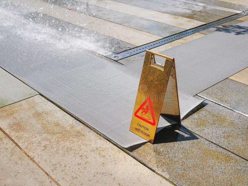Χρυσή στάση προειδοποίησης πατωμάτων προσοχής υγρή που στάζει πλησίον το νερό στο πάρκο στοκ φωτογραφίες