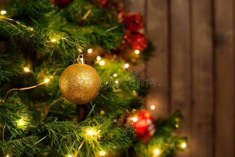 Χρυσή σφαίρα Χριστουγέννων σε ένα χριστουγεννιάτικο δέντρο στοκ φωτογραφίες